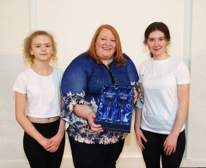 Naomi Long MEP receives Youth Lyric Belfast Crystal glasses from our students.